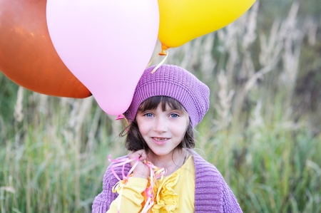 Outdoor portrait of little blue-eyed girl in violet hat holding bunch of balloons Stock Photo - 16494777