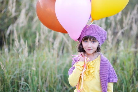 Outdoor portrait of little blue-eyed girl in violet hat holding bunch of balloons Stock Photo - 16494780