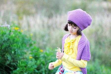 Outdoor portrait of little girl in violet hat holding daisies