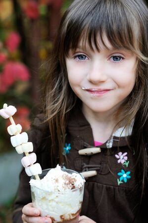Portrait of smiling little cute girl with a glass of hot chocolate Stock Photo - 16494761