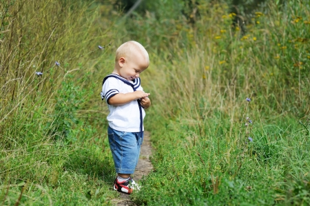 alone person: Cute baby boy in sailor outfit walking on meadow