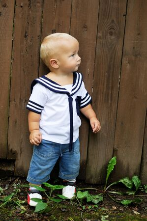 alone person: Cute baby boy in sailor outfit in front of wooden fence Stock Photo