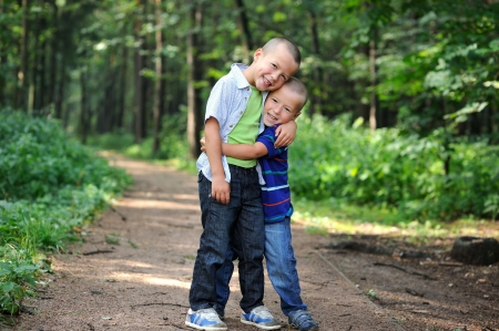 younger: Outdoor portrait of brothers standing together in the forest