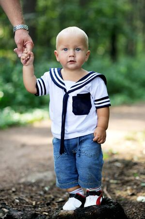 Cute baby boy in sailor outfit is holding parent's hand walking in forest photo