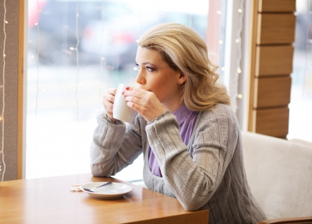 Portrait of young pretty woman drinking coffee in restaurant photo