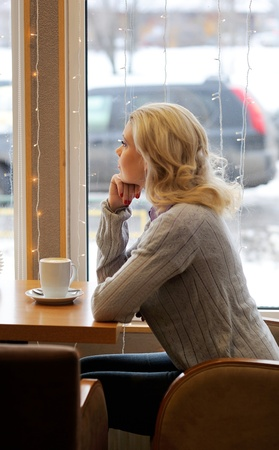 Young pretty woman sitting in cafe photo