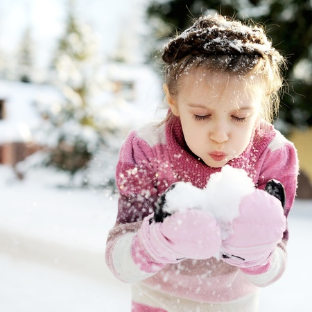 Little girl in pink dress playing with the snow outdoors photo