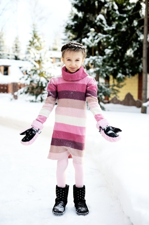 frost covered: Little girl in pink dress playing with the snow outdoors