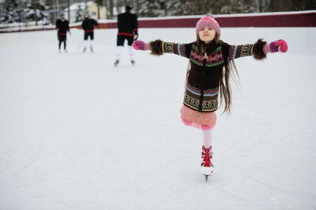 rink: Little girl having fun on ice skating rink outdoors Stock Photo