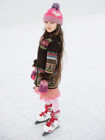 Little girl having fun on ice skating rink outdoors photo