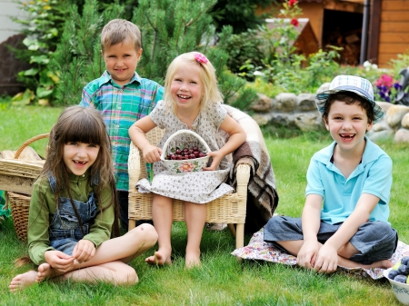 Group of happy children having picnic on a green lawn in front of country house