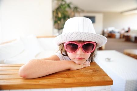petite fille triste: Portrait de petite fille sérieuse dans le chapeau blanc et des lunettes de soleil Banque d'images