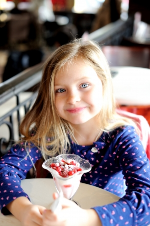 Adorable little girl eating ice cream at restaurant photo