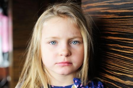 Portrait of adorable unhappy little girl photo