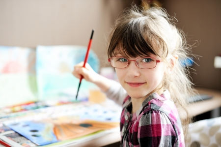 aquarelle painting art: Cute little girl painting a picture in home studio Stock Photo