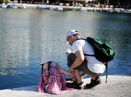 hunker: Young father and his daughter looking for small fishes in the water