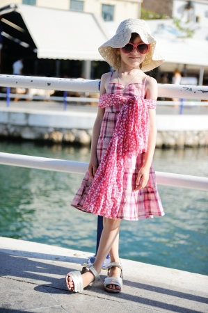 beach wrap: Beautiful little girl wearing pink dress, hat and sunglasses is ready for beach vacation Stock Photo