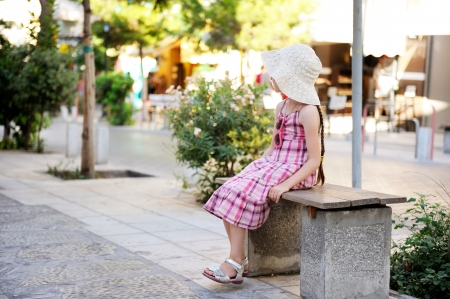 lost city: Beautiful little girl wearing pink dress, hat and sunglasses sitting on a bench Stock Photo