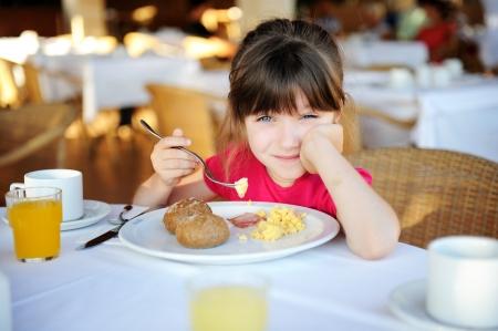 eating breakfast: Little sleepy girl eating breakfast in outdoor cafe Stock Photo
