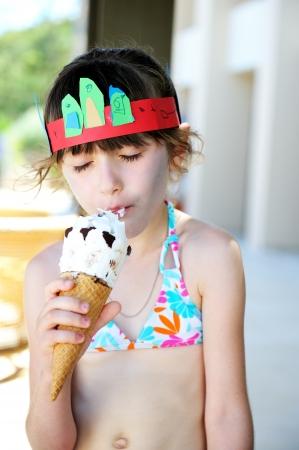 Cute brunette little girl in bathing suit eating ice cream Stock Photo