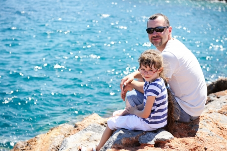 seafront: Young father and little daughter sitting on rocks near seafront Stock Photo