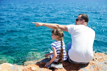Young father and little daughter sitting on rocks near seafront photo