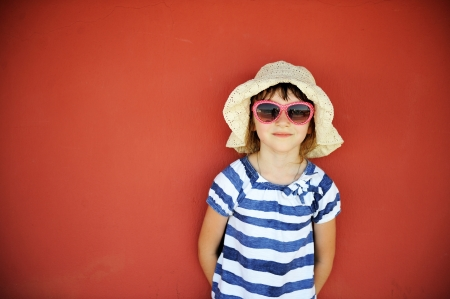 Portrait of serious little girl in white hat and sunglasses against a wall photo