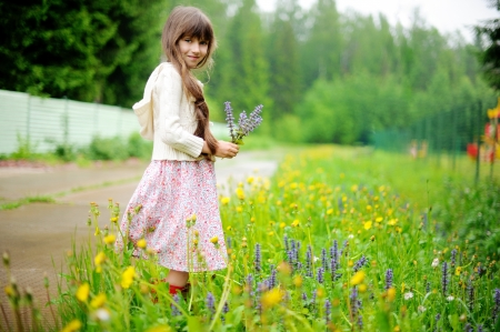 filed: Little girl picking up summer flowers on a meadow Stock Photo