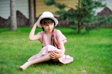 Amazing little girl posing outdoors in pink dress and white hat photo