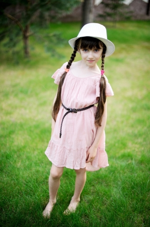 pink hat: Amazing little girl posing outdoors in pink dress and white hat