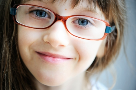 wearing glasses: Close-up portrait of brunette child girl in glasses
