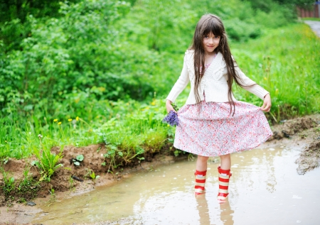 Elegant child girl in countrylike dress and red gumboots standing in a puddle on a rainy day