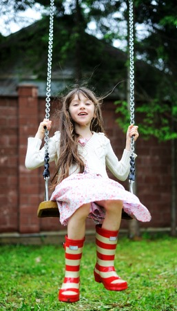 columpio: Chica niño elegante vestido countrylike y botas de goma roja balanceándose en el parque Foto de archivo
