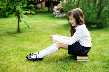 long socks: Young girl in school uniform sitting on stack of books Stock Photo