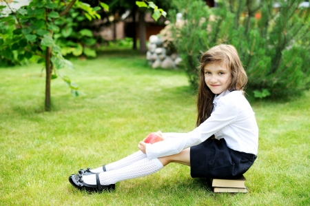 Young girl in school uniform sitting on stack of books Stock Photo