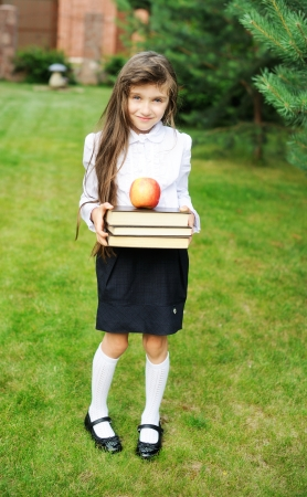 long socks: Young girl in school uniform holding stack of books with apple on top Stock Photo