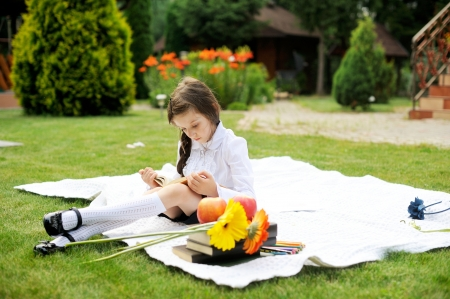 Cute schoolgirl in black and white uniform reading a book in the garden Stock Photo