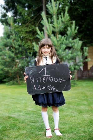 Nice young girl in navy school uniform writing on chalkboard in russian photo