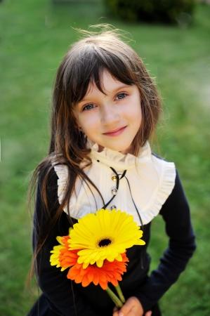 azul marino: Ni�a en azul marino uniforme escolar posando con flores amarillas y naranjas