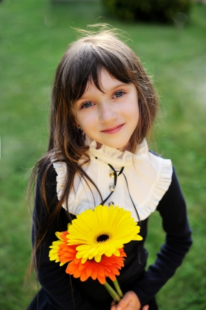 navy blue: Young girl in navy school uniform posing with yellow and orange flowers