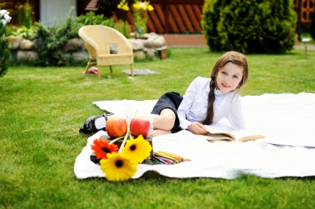 young schoolgirl: Cute schoolgirl in black and white uniform reading a book in the garden Stock Photo