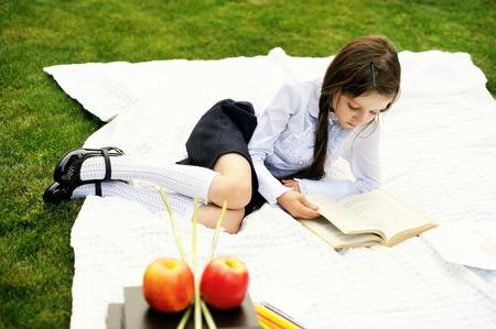 schoolgirl uniform: Cute schoolgirl in black and white uniform reading a book in the garden Stock Photo
