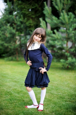 Cute school girl in navy uniform posing in a garden photo
