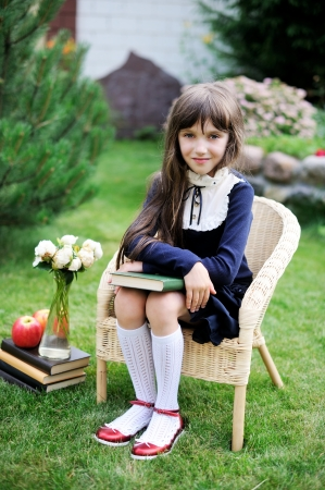 Cute young girl in navy school uniform sitting with a book in the garden photo