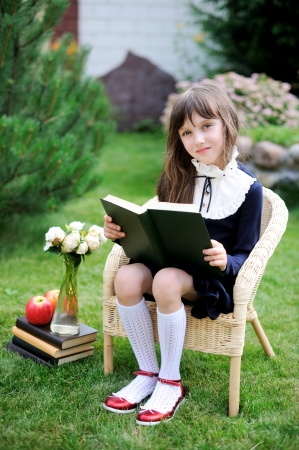 Cute young girl in navy school uniform reading a book in the garden photo