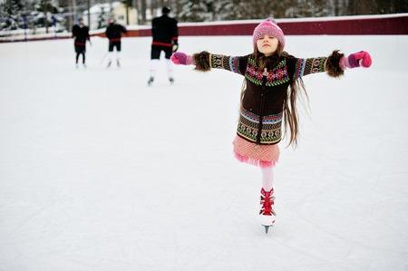 patinaje sobre hielo: Niña adorable en ropa de invierno y sombrero de bobble patinaje en pista de hielo