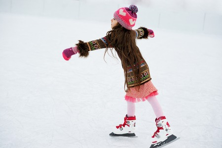 ice skating: Adorable little girl in winter clothes and bobble hat skating on ice rink Stock Photo