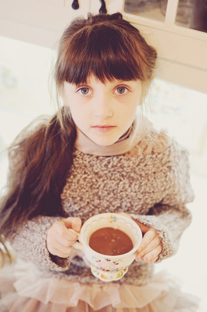 Child girl holding a vintage cup of hot drink, sepia tone added photo
