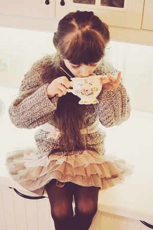 Child girl drinking from a vintage cup of hot drink, sepia tone added photo