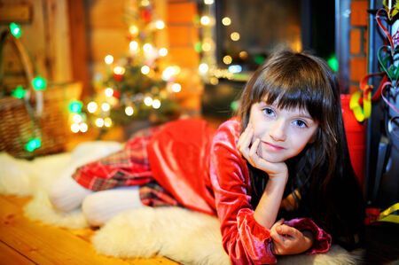 Child girl in red dress by a fireplace on Christmas photo